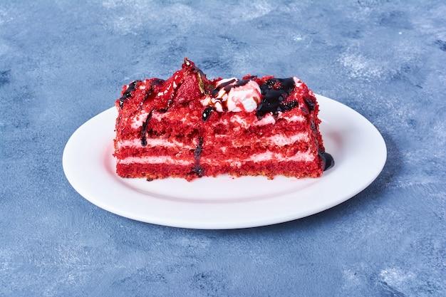 Een plakje rood fluwelen cake in een witte plaat