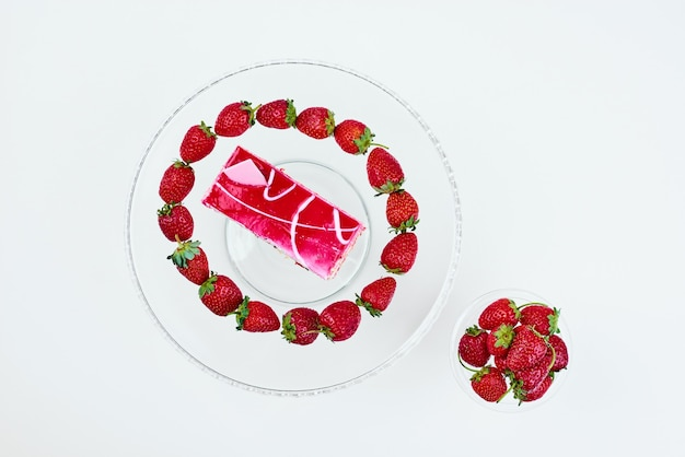 Een plakje roze cake met aardbeien.