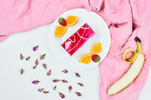 Een plakje roze cake met fruit, bovenaanzicht.
