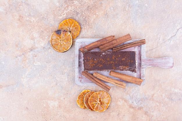 Een plakje tiramisu met kaneel en stukjes sinaasappel.
