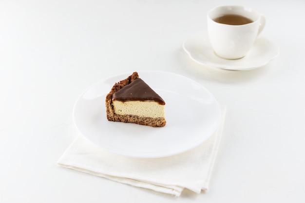 Een plakje tofu cake met gezouten karamel op een bord met een kopje thee.
