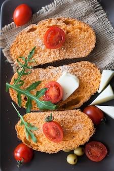 Een plakje tomatenbrood met kerstomaatjes en rucola op tafel