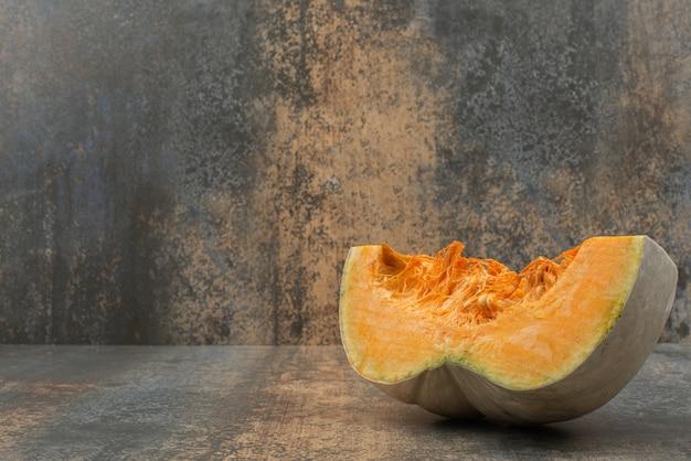 Een plakje verse gele pompoen op marmeren oppervlak