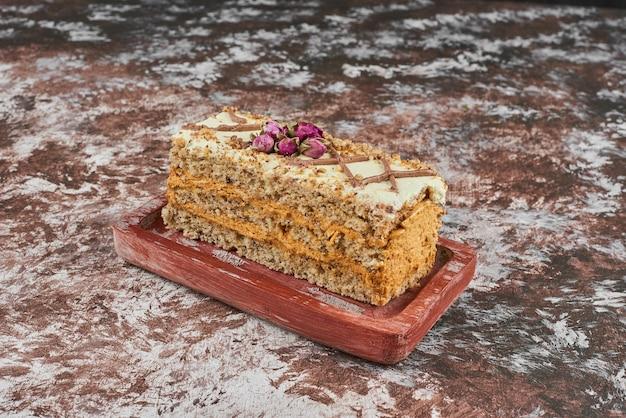 Een plakje walnootcake op een houten bord.