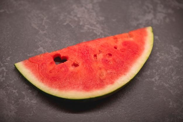 Een plakje watermeloen met een hartvormig gat