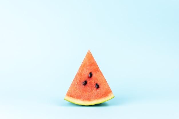 Een plakje watermeloen op pastelblauwe achtergrond
