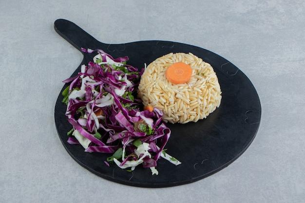 Een plakje wortel op de rijst naast salade, op het bord, op de marmeren achtergrond.