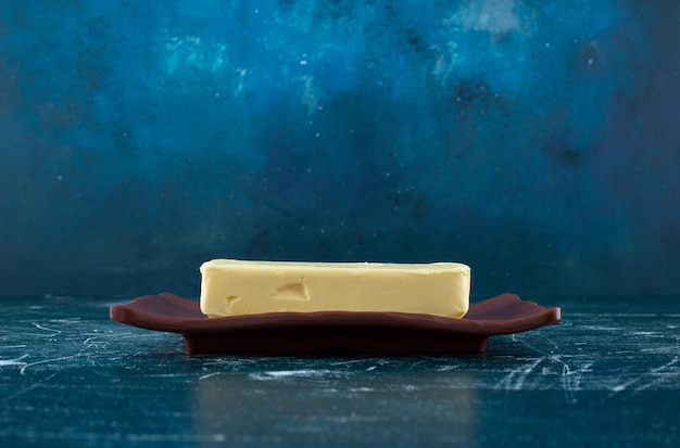 Een plakje zelfgemaakte boter op een aardewerken schotel.