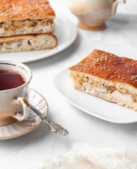 Een plakje zelfgemaakte kip en sesamtaart. op een witte plaat. in de buurt van een koffiepot en een kopje koffie. witte achtergrond.