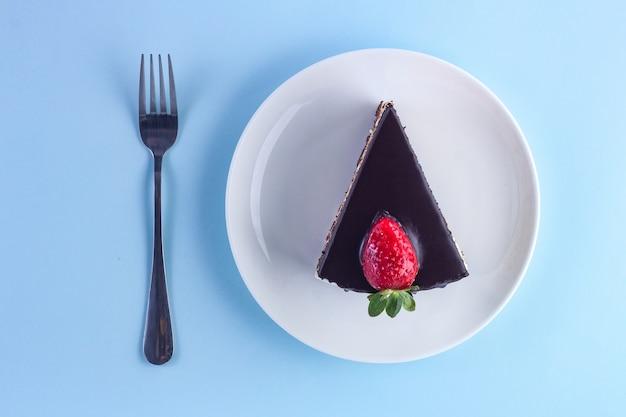 Een plakje zoete aardbeientaart met druipende chocoladeglans in een witte plaat en vork op blauw
