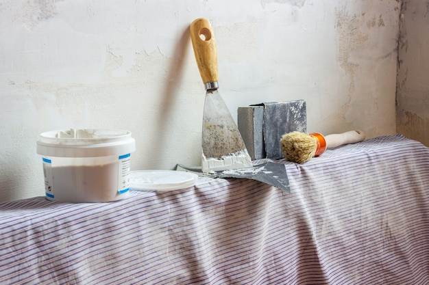 Een plamuurmes, kwast, schuurpapier en muurafdichtingspasta op een radiator klaar om de muren te renoveren. binnen.