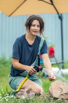 Een plant in de grond planten. een jonge vrouw plant een sappige bloem in de grond in een bloembed.