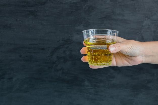 Een plastic beker met gele drank of olie vasthouden