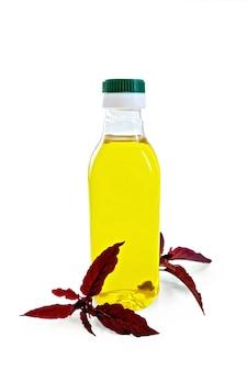 Een plastic fles olie met twee takken kastanjebruine amarant met een lichte schaduw op witte achtergrond
