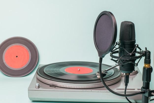 Een platenspeler met rode vinylplaten en een moderne microfoon.