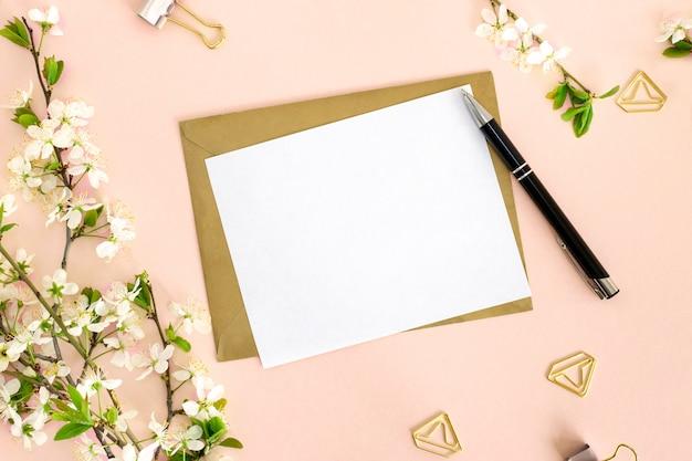 Een platliggende compositie met een mock-up van een witte blanco kaart voor tekst, een envelop van kraftpapier, een pen, kantoorclips en een tak van kers met bloemen op een roze achtergrond. bovenaanzicht.
