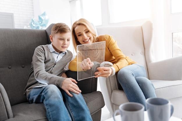 Een plezierige tijd. vrolijke positieve moeder en zoon zittend op de bank en kijken naar het tabletscherm terwijl ze thuis rusten