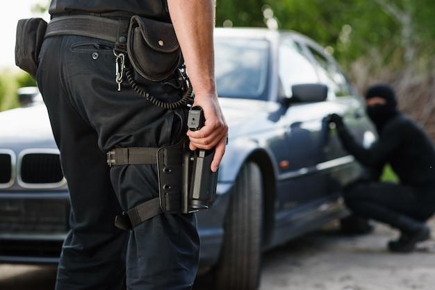 Een politieagent met een handpistool in zijn hand arresteerde een crimineel die een auto had gestolen. recht en rechtvaardigheid.
