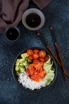 Een populair hawaiiaans gerecht, poke in een bord met rode vis, rijst en groenten. porplaat op een zwarte concrete achtergrond. bovenaanzicht.