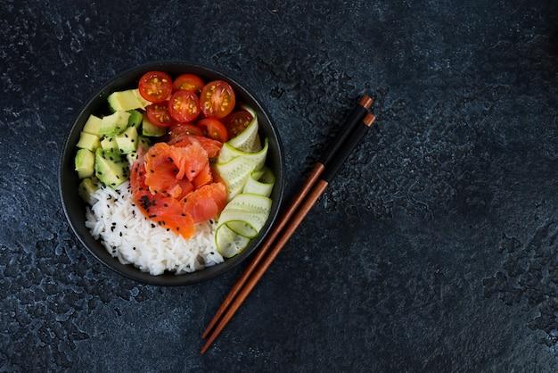 Een populair hawaiiaans gerecht, poke in een bord met rode vis, rijst en groenten. porplaat op zwarte concrete achtergrond met kopi-ruimte. bovenaanzicht.