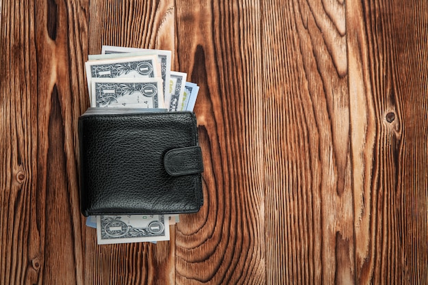 Een portemonnee met de amerikaanse dollars is geïsoleerd op een houten achtergrond
