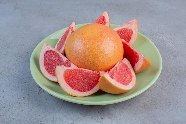Een portie grapefruit op een schotel op marmeren achtergrond.