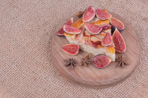 Een portie taart met paarse vijgen in een houten schotel
