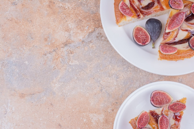 Een portie taart met paarse vijgen in een witte plaat