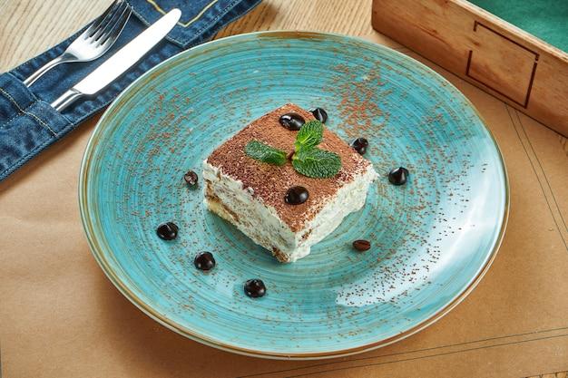 Een portie van klassieke italiaanse dessert - tiramisu op een blauw bord op een houten tafel. restaurant tafel instelling. lekker gebak