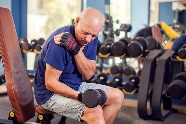 Een portret van de hogere mens die sterke schouderpijn voelt tijdens opleiding in de gymnastiek. mensen, gezondheidszorg en lifestyle concept