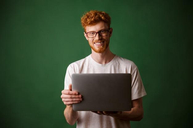 Een portret van de jonge readheadmens in witte laptop van de t-shirtholding