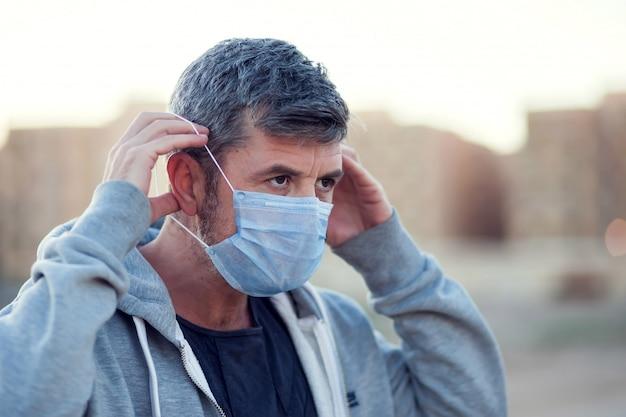 Een portret van de mens met medisch gezichtsmasker openlucht. mensen, gezondheidszorg en geneeskunde concept