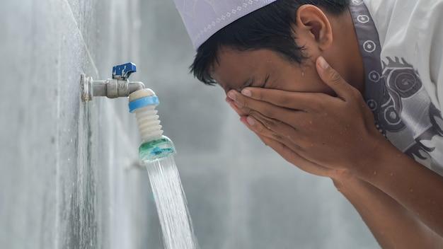 Een portret van een aziatische islamitische wassing bij moskee bidt vóór