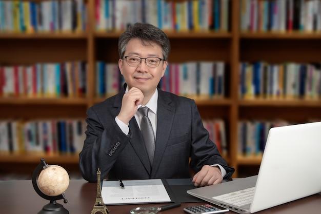 Een portret van een aziatische mannelijke zakenman op middelbare leeftijd die bij een bureau zit.