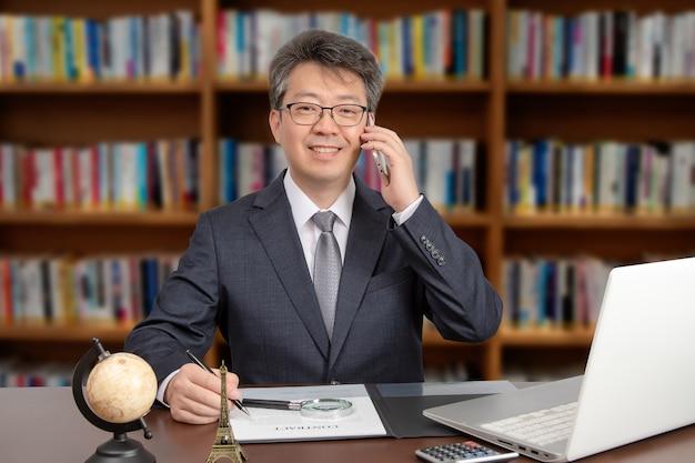 Een portret van een aziatische middelbare leeftijd mannelijke zakenman zittend aan een bureau, glimlachend en praten aan de telefoon.