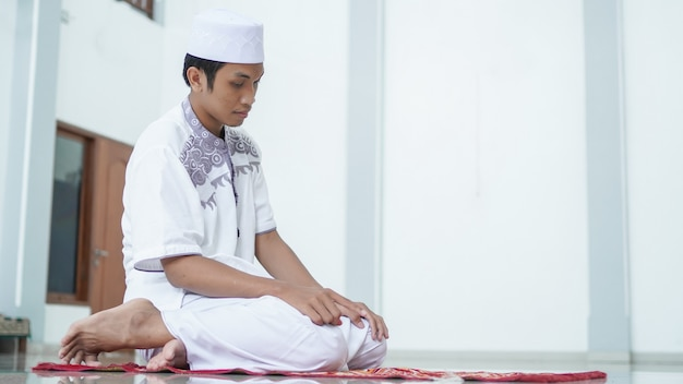 Een portret van een aziatische moslimman bidt in de moskee, de bidnaam is sholat, wat het einde van de sholat betreft