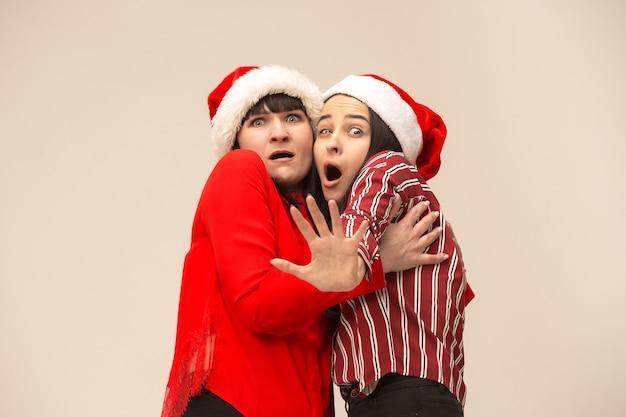Een portret van een bange moeder en dochter in kerstmuts op grijs