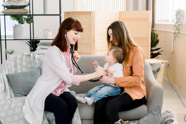 Een portret van een blanke vrouwelijke kinderarts met behulp van een stethoscoop onderzoekt een babymeisje in de handen van de moeder