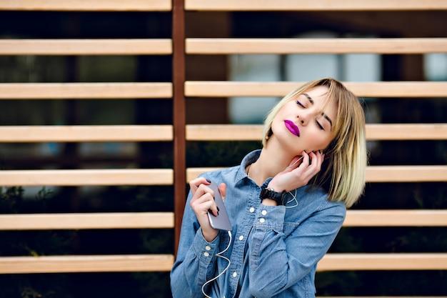 Een portret van een dromerig blond meisje met felroze lippen en naakt make-up en gesloten ogen, luisteren naar muziek op een smartphone met gestreepte houten balk achter