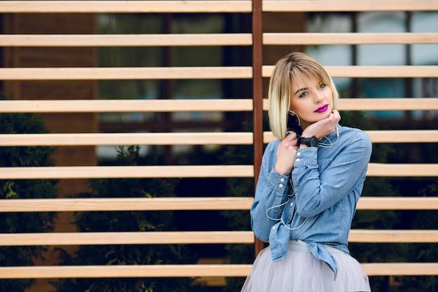 Een portret van een dromerig blond meisje met felroze lippen en naakt make-up, luisteren naar muziek op een smartphone met gestreepte houten balken achter