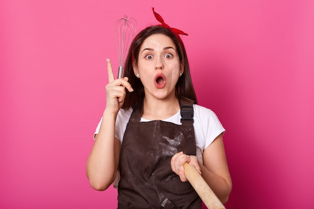 Een portret van een enthousiaste, energieke bakker die een klopper en deegroller in haar handen houdt, ziet er creatief en leuk uit, laat haar opstaan en opent haar mond wijd. nieuw idee van recept komt bij vrouwen op.