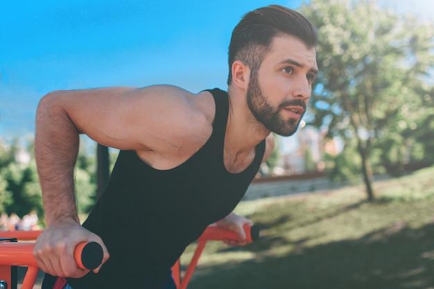 Een portret van een geconcentreerde gespierde bebaarde man in zwarte trainingskleding doet dips op parallelle staven. mans fitness met blauwe lucht op de achtergrond en open ruimte om hem heen. sport en crossfit.
