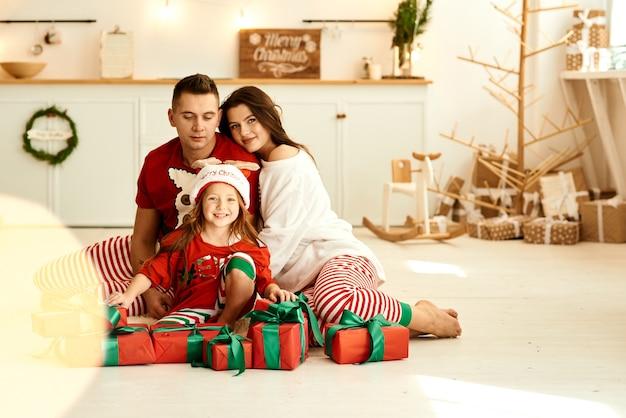 Een portret van een gelukkig gezin in de pyjama's in de keuken met een rode cadeautjes