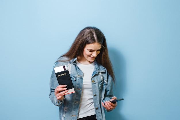 Een portret van een gelukkig meisje die met gebaren stellen en een paspoort met kaartje houden
