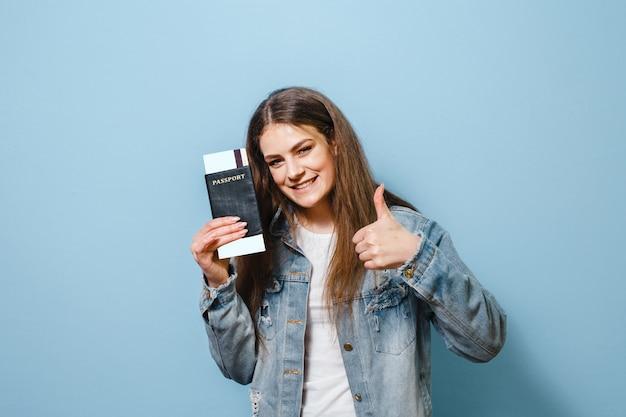 Een portret van een gelukkig meisje die met gebaren stellen en een paspoort met kaartje over blauwe achtergrond houden