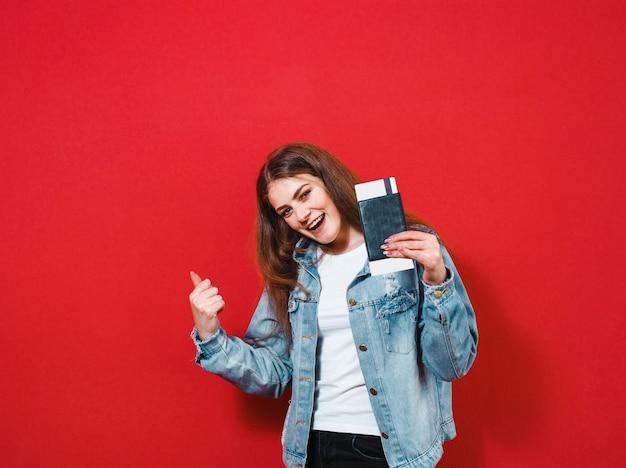 Een portret van een gelukkig meisje die met gebaren stellen en een paspoort met kaartje over een rode achtergrond houden