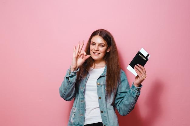 Een portret van een gelukkig meisje die met gebaren stellen en een paspoort met kaartje over roze achtergrond houden