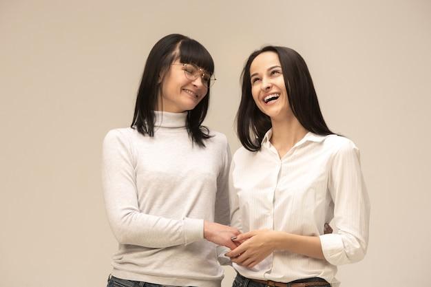 Een portret van een gelukkige moeder en dochter bij studio op grijs