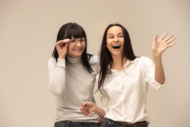 Een portret van een gelukkige moeder en dochter bij studio op grijze achtergrond. menselijke positieve emoties en gezichtsuitdrukkingen concept