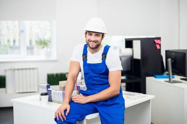 Een portret van een glimlachende bouwplaats supervisor in het kantoor